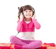 La muchacha con los auriculares es escucha la música Fotos de archivo libres de regalías