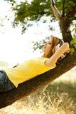 La muchacha con los auriculares miente sobre árbol Imágenes de archivo libres de regalías