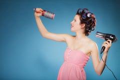 La muchacha con los bigudíes en pelo lleva a cabo el hairdreyer Imagenes de archivo