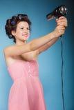 La muchacha con los bigudíes en pelo lleva a cabo el hairdreyer Imágenes de archivo libres de regalías