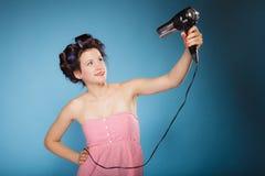 La muchacha con los bigudíes en pelo lleva a cabo el hairdreyer Foto de archivo