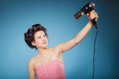 La muchacha con los bigudíes en pelo lleva a cabo el hairdreyer Foto de archivo libre de regalías