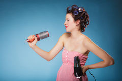 La muchacha con los bigudíes en pelo lleva a cabo el hairdreyer Imagen de archivo