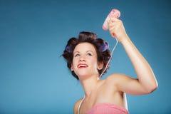 La muchacha con los bigudíes en pelo lleva a cabo el hairdreyer Fotos de archivo