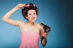 La muchacha con los bigudíes en pelo lleva a cabo el hairdreyer Imagen de archivo libre de regalías