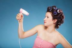 La muchacha con los bigudíes en pelo lleva a cabo el hairdreyer Fotografía de archivo
