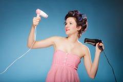 La muchacha con los bigudíes en pelo sostiene hairdreyers Fotografía de archivo