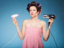 La muchacha con los bigudíes en pelo sostiene hairdreyers Imagen de archivo