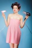 La muchacha con los bigudíes en pelo sostiene hairdreyers Fotos de archivo libres de regalías