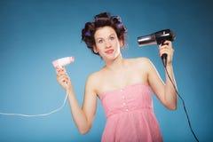 La muchacha con los bigudíes en pelo sostiene hairdreyers Fotografía de archivo libre de regalías