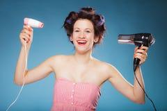 La muchacha con los bigudíes en pelo sostiene hairdreyers Imagen de archivo libre de regalías