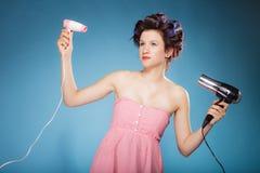 La muchacha con los bigudíes en pelo sostiene hairdreyers Foto de archivo