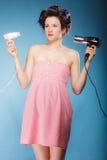 La muchacha con los bigudíes en pelo sostiene hairdreyers Imagenes de archivo