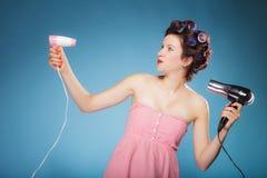 La muchacha con los bigudíes en pelo sostiene hairdreyers Imágenes de archivo libres de regalías