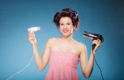 La muchacha con los bigudíes en pelo sostiene hairdreyers Fotos de archivo
