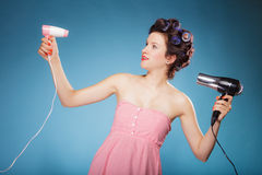 La muchacha con los bigudíes en pelo sostiene hairdreyers Foto de archivo libre de regalías