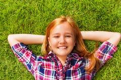 La muchacha con los brazos bajo su cabeza pone en hierba verde Fotos de archivo libres de regalías
