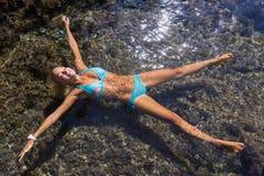 La muchacha con los brazos extendidos y las piernas aparte miente en el agua imágenes de archivo libres de regalías