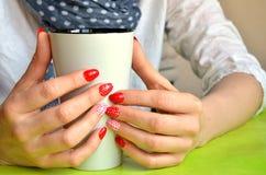 La muchacha con los clavos rojos en sus fingeres sostiene la taza blanca, primer Fotografía de archivo libre de regalías
