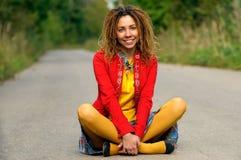 La muchacha con los dreadlocks se sienta en el asfalto Foto de archivo