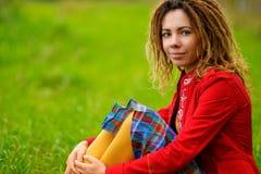 La muchacha con los dreadlocks se sienta en hierba Imagenes de archivo