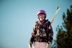 La muchacha con los esquís encendido mueve hacia atrás Imagenes de archivo