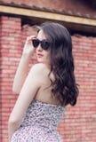 La muchacha con los labios rojos en las gafas de sol da vuelta alrededor cerca del ladrillo Foto de archivo libre de regalías