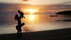 La muchacha con los niños va en paseos y juego en la playa durante puesta del sol metrajes