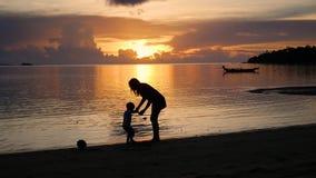 La muchacha con los niños va en paseos y juego en la playa durante puesta del sol almacen de metraje de vídeo