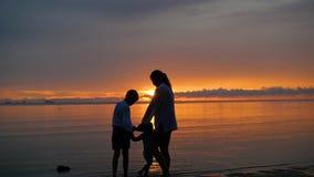 La muchacha con los niños va para los paseos y el juego en la playa en el tiempo de la puesta del sol almacen de video