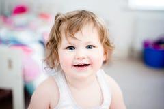 La muchacha (3) con los ojos azules brillantes sonríe en la cámara Fotografía de archivo