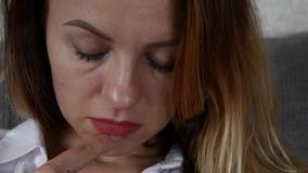 La muchacha con los ojos rasgón-manchados lee el mensaje en su smartphone almacen de metraje de vídeo