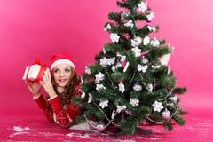 La muchacha con los regalos acerca al árbol de navidad Imagen de archivo