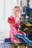 La muchacha con los regalos acerca a un árbol del Año Nuevo Foto de archivo libre de regalías