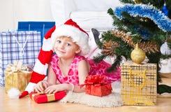 La muchacha con los regalos acerca a un árbol del Año Nuevo Foto de archivo