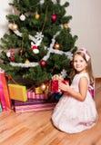 La muchacha con los regalos acerca a un abeto Foto de archivo