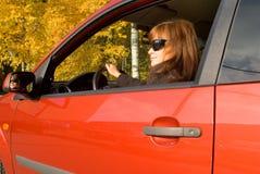 La muchacha con los sunglass en el coche rojo Foto de archivo libre de regalías