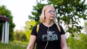La muchacha con los vidrios está en el parque que sostiene un libro en sus manos Igualaci?n de la caminata en el parque Es agrada almacen de video