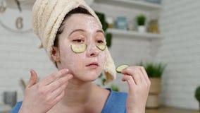 La muchacha con la máscara en cara puso rebanadas del pepino debajo de ojos almacen de metraje de vídeo