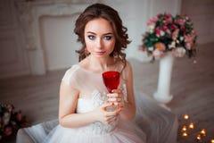 La muchacha con maquillaje en un vestido de boda rosado se está sentando en un cuarto hermoso rodeado por las flores y las velas  Foto de archivo libre de regalías