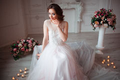 La muchacha con maquillaje en un vestido de boda rosado se está sentando en un cuarto hermoso rodeado por las flores y las velas Imagen de archivo