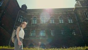 La muchacha con la mochila está caminando a lo largo del edificio histórico con Sun Ray y llamarada almacen de video
