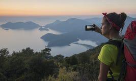 La muchacha con la mochila está tomando imágenes magníficas de la puesta del sol con ayuda Imágenes de archivo libres de regalías
