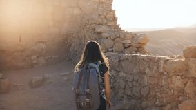 La muchacha con la mochila explora ruinas antiguas del desierto La mujer bonita camina entre las paredes de la fortaleza de la mo almacen de metraje de vídeo