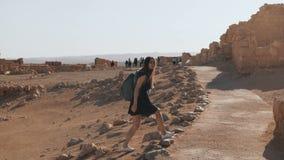 La muchacha con la mochila explora ruinas del desierto El viajero femenino bastante europeo camina entre paisaje antiguo Masada I almacen de metraje de vídeo