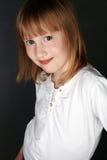 La muchacha con pecas y un pelo justo, sonriendo levemente, mira Fotografía de archivo