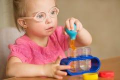 La muchacha con Síndrome de Down vierte el agua mediante los tubos del enema en un tubo de ensayo Fotografía de archivo