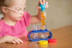 La muchacha con Síndrome de Down vierte el agua mediante los tubos del enema en un tubo de ensayo Imágenes de archivo libres de regalías