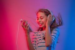 La muchacha con smartphone y los auriculares escucha la música Fotografía de archivo