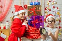 La muchacha con sorpresa muestra en el reloj en el Año Nuevo, Papá Noel que sonríe feliz desempaquetando los regalos Imagenes de archivo
